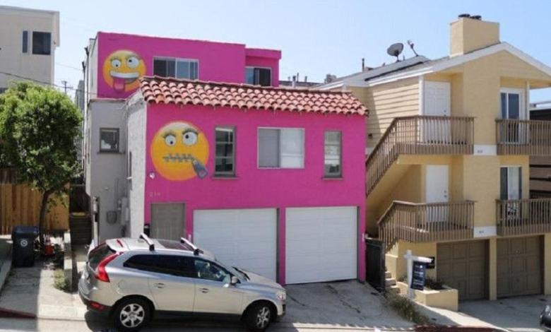 Photo of Bright pink house decorated with emojis is result of neighbor's quarrel