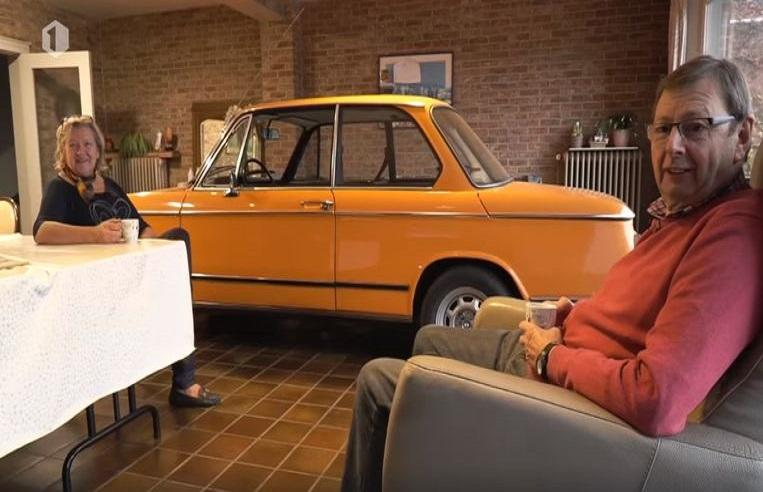 Couple drives oldtimer into living room, look on it instead of TV
