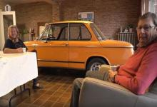 Photo of Couple drives oldtimer into living room, look on it instead of TV