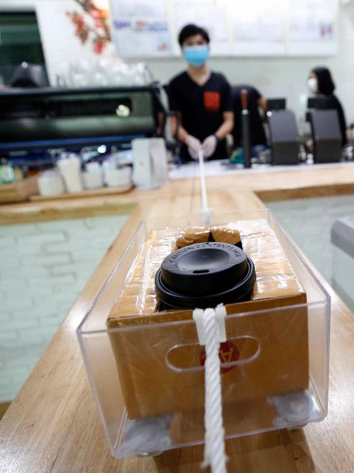 In coffee bar Art of Coffee in Bangkok, keeping your distance is sacred. Employees have devised an ingenious system to provide customers with a cup of coffee.