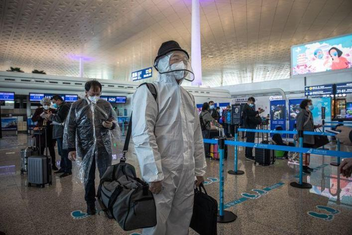 Passengers appear in protective suits
