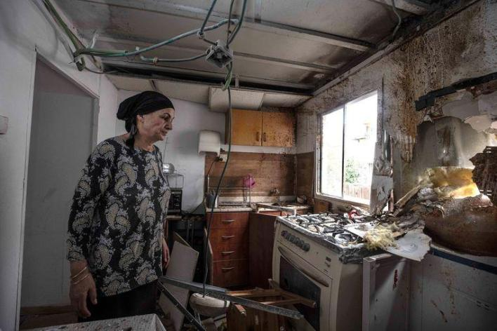 A resident of Sderot measures the damage to her house after a missile attack from the Gaza Strip.