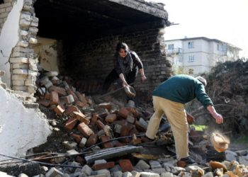 Vjollca Mesiti (L), 49, and Meleq Mesiti, 53, rummage through the ruins of their bakery to salvage bread baking pans in Thumane, northwest of the capital Tirana, on January 31, 2020. – A 6,4 magnitude quake shook Albania on November 26, 2019, the most deadly and destructive in four decades, leaving 51 lives lost and more than 15,000 people displaced. Nearly 90 buildings were reduced to rubble while more than 80,000 were damaged. The most damaged area was Albania's second city of Durres, on the Adriatic coast, and the nearby town of Thumane, where scores of people were trapped beneath the ruins of apartment buildings and hotels. As the country struggles to put the pieces back together, it is facing a structural reality that the disaster exposed: the scourge of illegal construction that has allowed unsafe homes to sprout up across the poor Balkan country. (Photo by Gent SHKULLAKU / AFP)