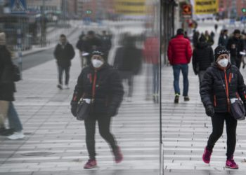A woman wearing a protective mask is pictured reflected on a window in Stockholm, Sweden, where primary schools, restaurants and bars are open and people encouraged to go outside for a nip of air, while the rest of Europe is in lockdown in a bid to curb the spread of COVID-19, on March 24, 2020. - The country's milder tone and measures are in stark contrast to the increasingly alarmist cries from many other countries and international agencies, and have sparked a heated debate in the country about whether Sweden is doing the right thing. (Photo by Jonathan NACKSTRAND / AFP)