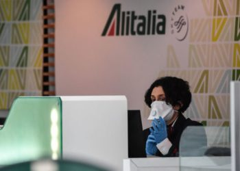 An airport Alitalia staff, wearing a respiratory mask and gloves, looks on at Rome's Fiumicino international airport March 13, 2020. – Rome's Ciampino airport will shut to passenger flights from March 13, authorities said, with a Terminal T1 also closing at the city's main Fiumicino facility next week as airlines slash flights to Italy over the coronavirus outbreak. (Photo by Andreas SOLARO / AFP)