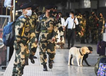"""Indian security personnel wearing facemasks amid concerns over the spread of the COVID-19 novel coronavirus, stand guard at the platform upon arrival of the """"Maitree Express"""" train, which connects Dhaka in Bangladesh to India, in Kolkata on March 14, 2020. India with its 1.3 billion population and proximity to China has so far come through the global virus crisis relatively unscathed with just 81 reported cases. Dibyangshu SARKAR / AFP"""