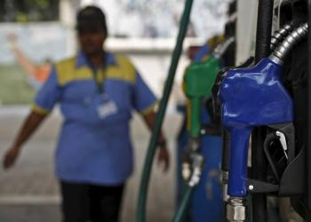 An employee stands next to a fuel pump at a fuel station. PHOTO: REUTERS/ADNAN ABIDI
