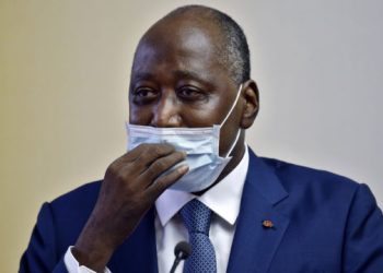 "Ivory Coast Prime Minister and ruling party's candidate in the October 2020 presidential election Amadou Gon Coulibaly, wearing a protective face mask, delivers a speech to members of the government upon his arrival at Felix Houphouet Boigny Airport after ""recovering"" in France following heart problems in Abdijan on July 2, 2020. (Photo by SIA KAMBOU / AFP)"