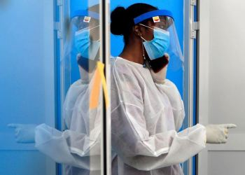 A healthcare worker wearing protective gear talks on a mobile phone at a testing center for COVID-19 at the Institute for Health Research, Epidemiological Surveillance and Training (IRESSEF), in Dakar, Senegal July 24, 2020. REUTERS/Zohra Bensemra