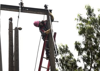 A technician fixes a power supply cable on a pole in Ilupeju district of Lagos, on September 8, 2020. – The Nigerian government has dumped a decade-long pricing regime for petrol and electricity allowing marketers to fix prices resulting in anger and tension in the oil-rich Africa's most populous country of 200 million people. (Photo by PIUS UTOMI EKPEI / AFP)