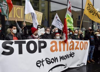 """Demonstrators hold a banner reading """"Stop Amazon and its world"""" and wave flags as they gather to protest against Amazon implantation, in front of the Perpignan Mediterranee Metropole headquarters in Perpignan, on January 30, 2021. (Photo by RAYMOND ROIG / AFP)"""