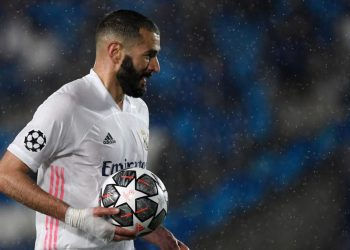 Real Madrid's French forward Karim Benzema holds the ball as he celebrates his goal during the UEFA Champions League semi-final first leg football match between Real Madrid and Chelsea at the Alfredo di Stefano stadium in Valdebebas, on the outskirts of Madrid, on April 27, 2021. (Photo by PIERRE-PHILIPPE MARCOU / AFP)