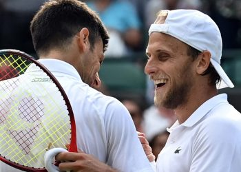 Serbia's Novak Djokovic (L) greets US player Denis Kudla after winning their men's singles third round match on the fifth day of the 2021 Wimbledon Championships at The All England Tennis Club in Wimbledon, southwest London, on July 2, 2021. (Photo by Glyn KIRK / AFP)