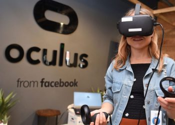 """(FILES) In this file photo taken on October 23, 2019, Facebook employee Elza Uzmanoff tries out an Oculus device at the company's corporate headquarters campus in Menlo Park, California. – Facebook on August 19, 2021, unveiled technology for """"workrooms,"""" allowing remote collaboration for people using its Oculus virtual reality gear.The """"Horizon Workrooms"""" project allows users to switch back and forth from virtual reality to web conferencing to adapt to different situations. (Photo by Josh Edelson / AFP)"""