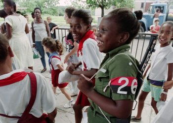 A young school girl dressed in green uniform and wearing a Cuban revulutionary arm band for a shool play, laughs with school mates on her way to the last day of school before summer vacation on July 7 , 1995 at Havana. School students, who receive free education, are instructed in the Marxist and Leninist doctrine since the first grade. (Photo by Roberto SCHMIDT / AFP)