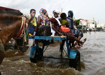 Horses pull carts with passengers through flooded streets after heavy rain in Dakar on August 22, 2021. (Photo by SEYLLOU / AFP)
