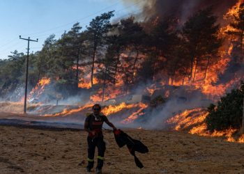 A firefighter walks ahead of a wildfire on August 2, 2021 in Mugla, Marmaris district, as the European Union sent help to Turkey and volunteers joined firefighters in battling a week of violent blazes that have killed eight people. – Turkey's struggles against its deadliest wildfires in decades come as a blistering heatwave grips southeastern Europe creating tinderbox conditions that Greek officials blame squarely on climate change. The fires tearing through Turkey since July 28 have destroyed huge swathes of pristine forest and forced the evacuation of panicked tourists from seaside hotels. (Photo by Yasin AKGUL / AFP)