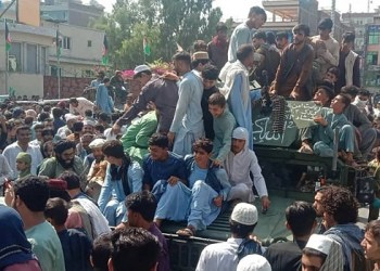 Taliban fighters and local people sit on an Afghan National Army (ANA) humvee vehicle on a street in Jalalabad province on August 15, 2021. (Photo by – / AFP)