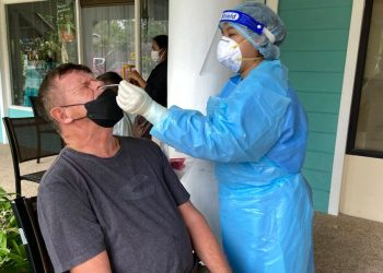 """This picture taken on September 20, 2021 shows a medical staff member dressed in personal protective equipment (PPE) as she conducts a swab test in Phuket, as tourists take advantage of the """"Phuket Sandbox"""" programme for visitors fully vaccinated against the Covid-19 coronavirus. (Photo by Dene CHEN / AFP)"""
