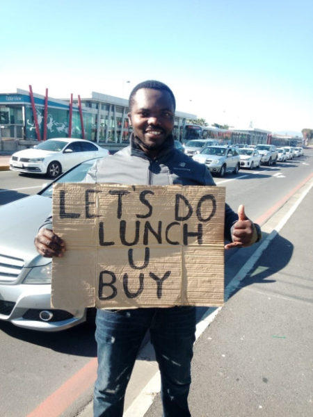 Funny unemployed Dad who entertains people with placards receives help