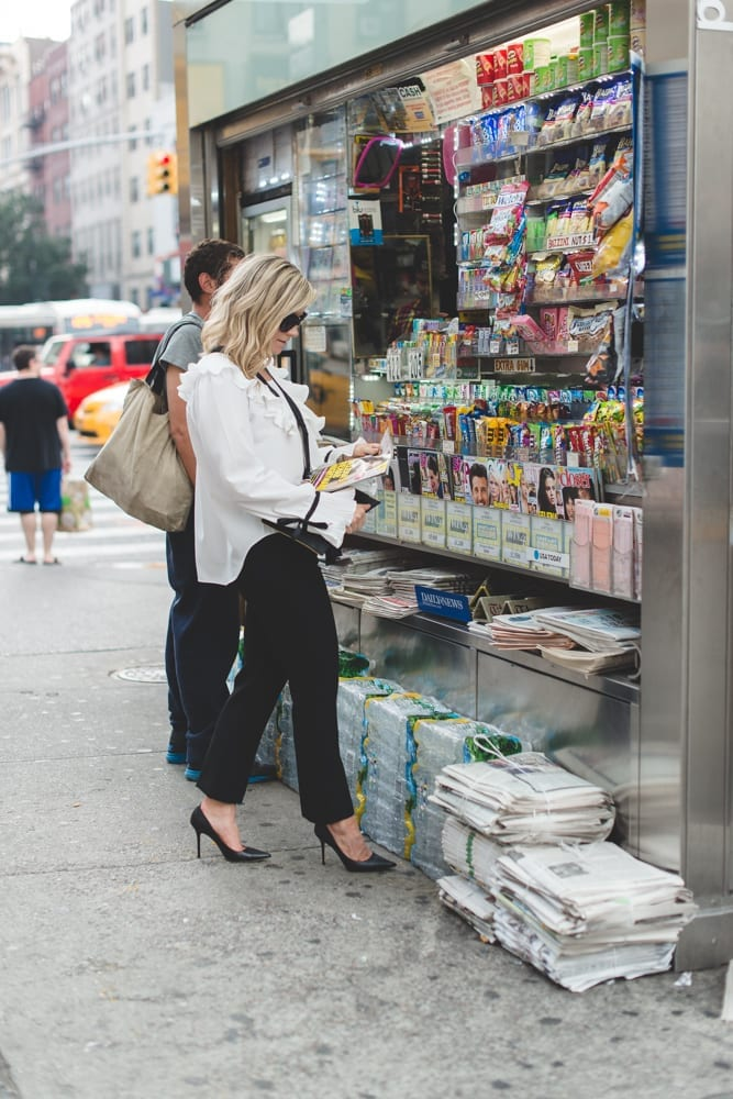 Blogger, Ashley Pletcher browses a newsstand for the latest celebrity gossip wearing an Asos ruffle top with Express pants and Jimmy Choo Pumps for NYFW!