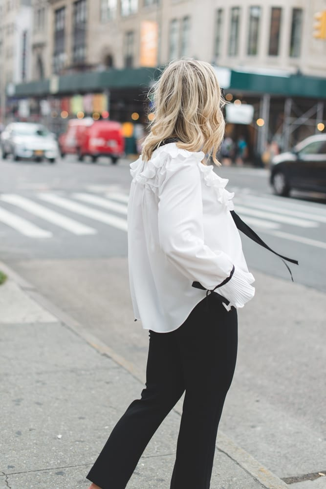 Blogger, Ashley Pletcher shows us how to be trendy but still affordable while wearing an Asos ruffle top with Express pants and Jimmy Choo Pumps!
