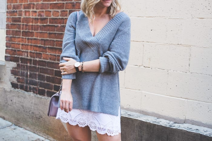 Fashion Blogger, Ashley Pletcher starts transitioning clothing into a Fall wardrobe by pairing an Abercrombie & Fitch summer skirt with some black booties and a Nordstrom deep v-neck sweater, and a classic Daniel Wellington watch.