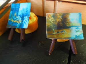 Edible paintings and their chocolate stands, resting on Lemon Meringue