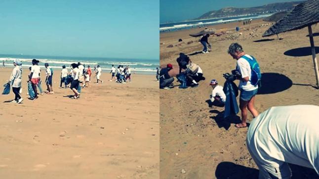 """سياح أجانب يلتئمون في حملة لتنظيف شاطئ أكادير من """"أزبالنا"""" (صور)"""