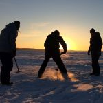 Researchers drill a hole to sink a hydrophone into an ice-covered lake.