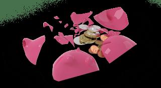 Broken piggy bank with some coins