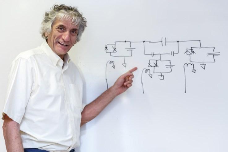 <p>John Martinis posa en elICMAT delante de un esquema de circuitos dibujado por él mismo./ Álvaro Muñoz Guzmán (SINC)</p>