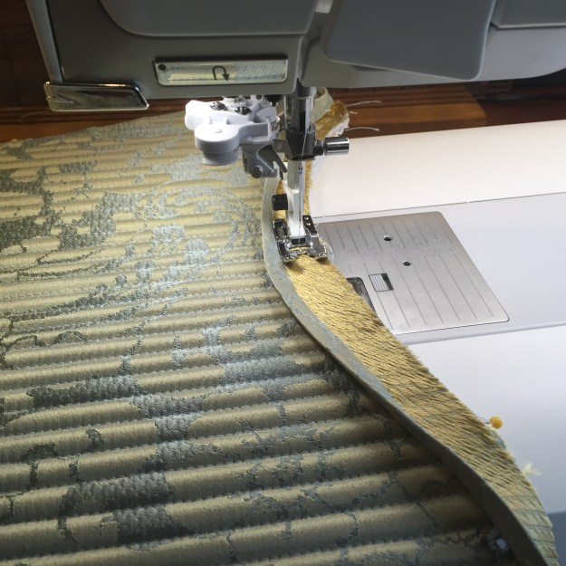 Binding the stomacher by machine - the inside will be sewn down by hand.