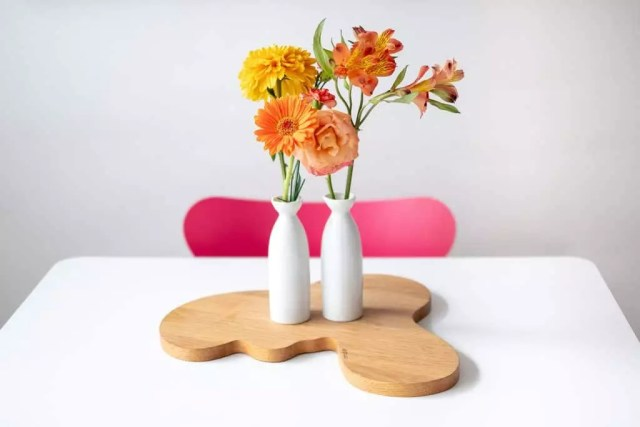 Orange and yellow flowers in small white vases