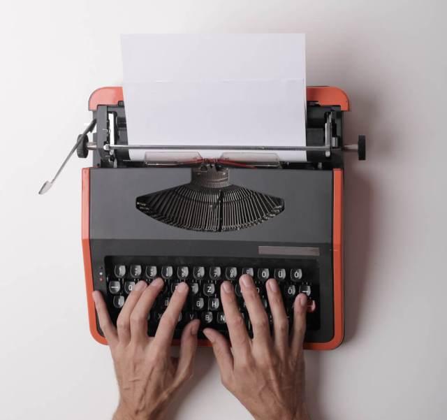 Hände auf Schreibmaschine mit noch leerem Blatt