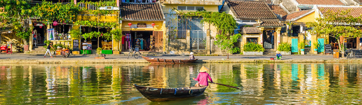 Locals paddling Vietnamese boats down river in Hoi An