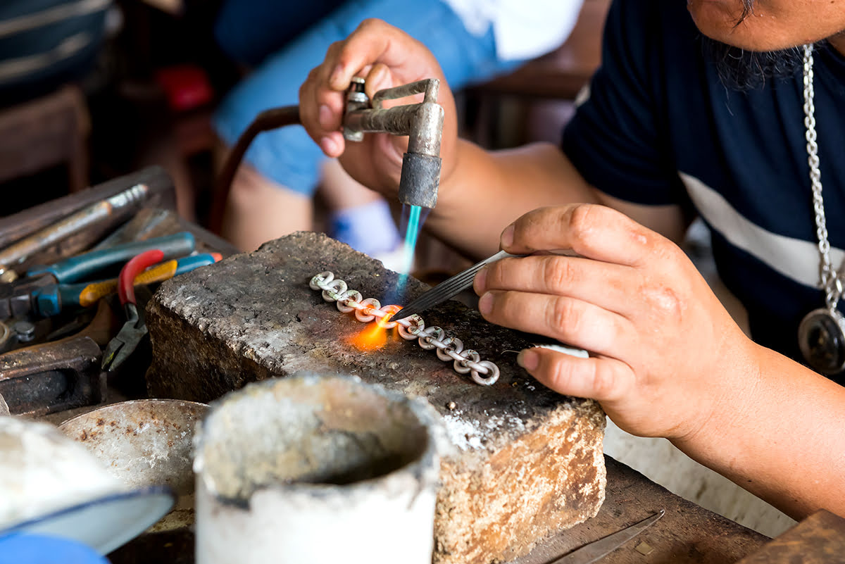 Blacksmith soldering traditional jewelry in Bali, Indonesia