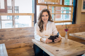 Aurora Geis, professional coaching consultant getting work down while sitting down at a coffee shop enjoying a cup of coffee and reading something off of her phone. She is wearing a white blouse and there is a purple flower on the table.
