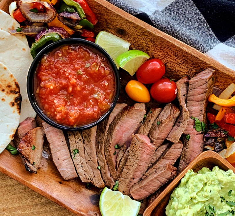 wooden board with sliced steak, guacamole, salsa, tortillas and grilled vegetables