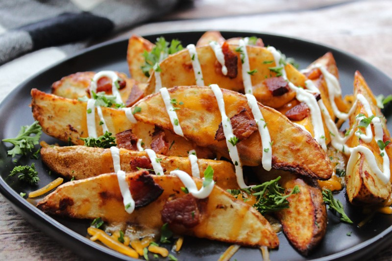 black plate with loaded potato wedges with cheese, bacon and sour cream
