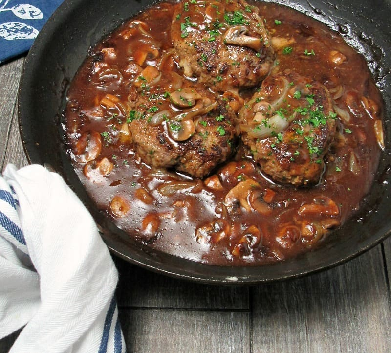 beef patties in skillet with gravy, mushrooms and onions