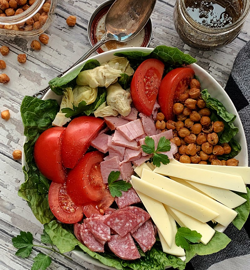 overhead view antipasto salad, jar of dressing and spoon