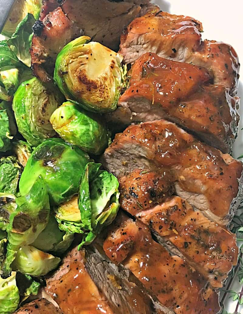 sliced pork tenderloin on white plate with brussels sprouts