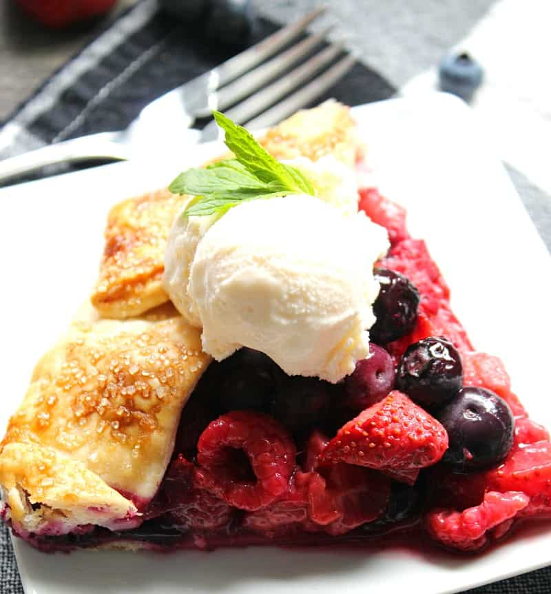 slice of galette topped with a scoop of vanilla ice cream and garnished with mint leaves