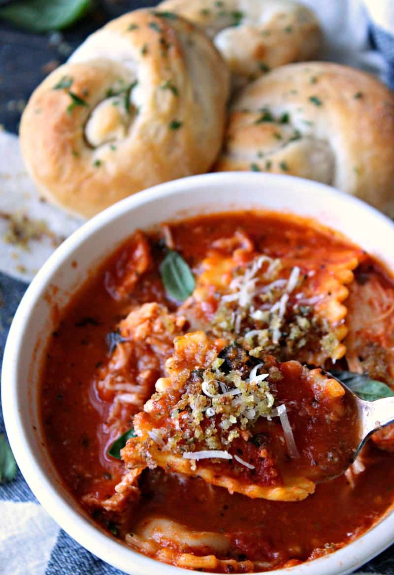 Bowl of soup topped with breadcrumbs served with butter garlic knots