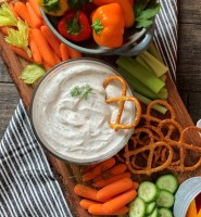 overhead view bowl of dill dip surrounded by bright colored chopped vegetables