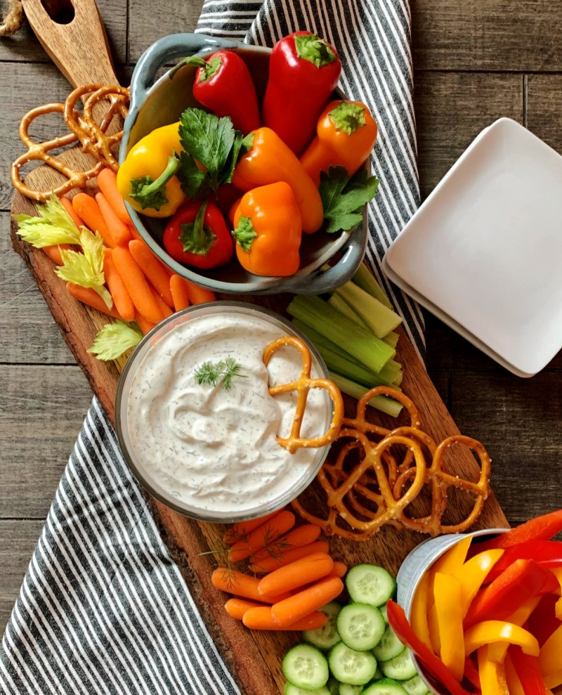 overhead view of clear bowl of dill dip with pretzels and bright colored vegetables
