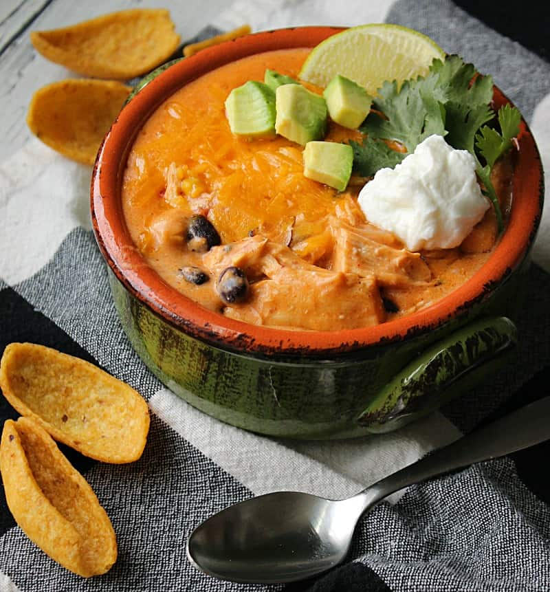 bowl of crockpot chicken enchilada soup topped with sour cream and cheese