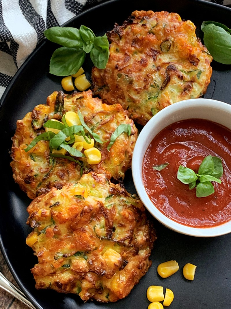 3 zucchini corn fritters on black plate with marinara for dipping