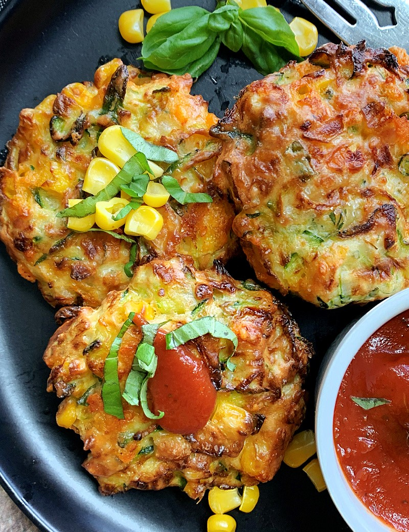 zucchini corn fritters on black plate garnished with basil